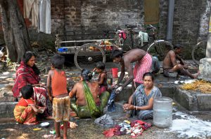 KOLKATA, INDIA - 27 OCTOBER, 2009: An unidentified group of Indian people wash themselves on a street of Kolkata on October 27, 2009. The homeless living on the street cause serious problems in every bigger city of India.